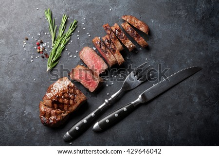 Grilled sliced beef steak on stone table. Top view