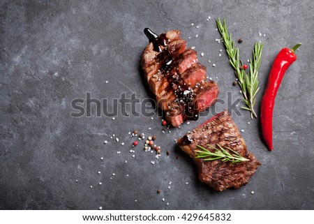 Grilled sliced beef steak with balsamico and rosemary on stone table. Top view with copy space - stock photo