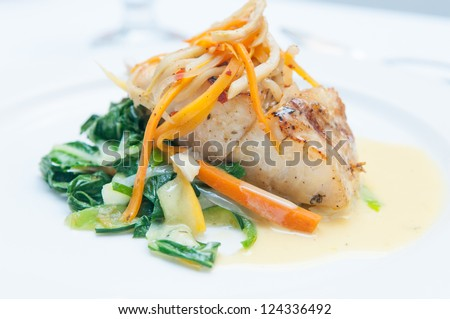 grilled snapper with sauteed vegetables and a creamy fish sauce - stock photo