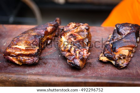 Grilled spare beef or pork back ribs prepared in smoker. Delicious roasted cuts of meet made on barbecue smoker on a wooden cutting desk.