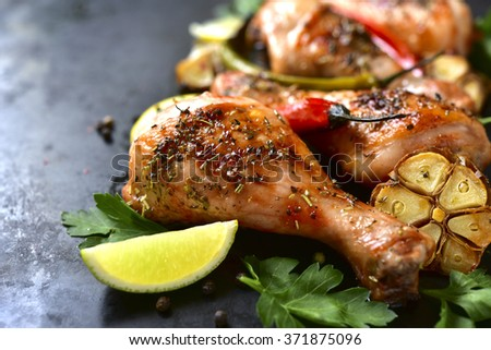 Grilled spicy chicken legs on a black background. - stock photo