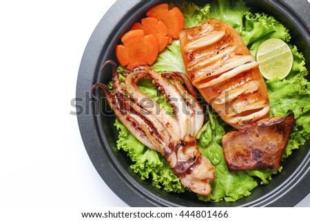Grilled squid and vegetable on frying pan over white background - stock photo