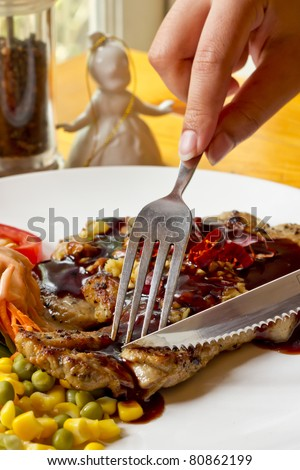 Grilled Steak Cutting with Knife and Fork - stock photo