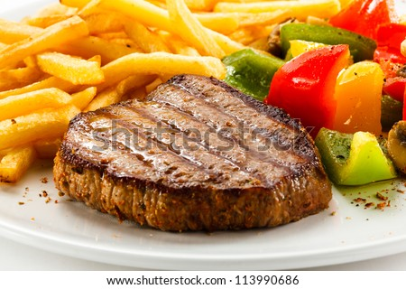 Grilled steak, French fries and vegetables - stock photo