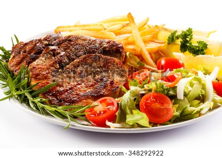 Grilled steak, French fries and vegetables on white background  - stock photo