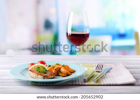 Grilled steak, grilled vegetables and fried potato pieces on table, on bright background - stock photo