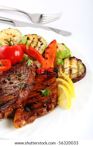Grilled steak meat with vegetables on a white background - stock photo