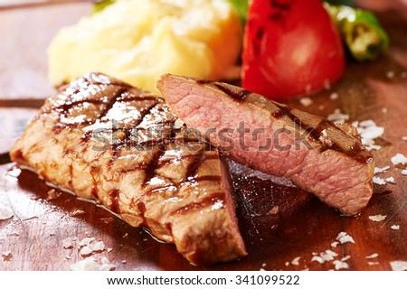 grilled steak on a wooden service plate with vegetable garnishes