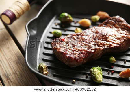 Grilled steak on grill pan with wine on wooden table - stock photo