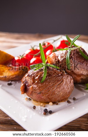 Grilled steak on wood and fresh vegetable.
