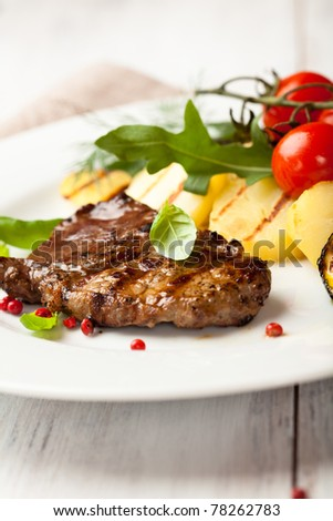 Grilled steak with pink peppercorns and grilled vegetables - stock photo