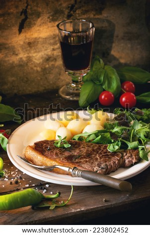Grilled steak with potatoes and green salad on white ceramic plate and vintage glass with red wine over old wooden table. See series - stock photo