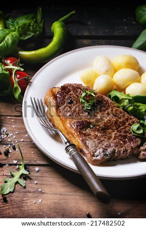 Grilled steak with potatoes and green salad on white ceramic plate over old wooden table. See series - stock photo
