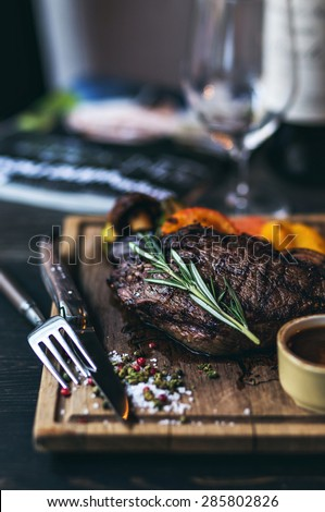 Grilled Steak with salt and pepper on meat cutting board with grilled vegetables and wine on dark wooden background. Bottle of red wine on the background. - stock photo