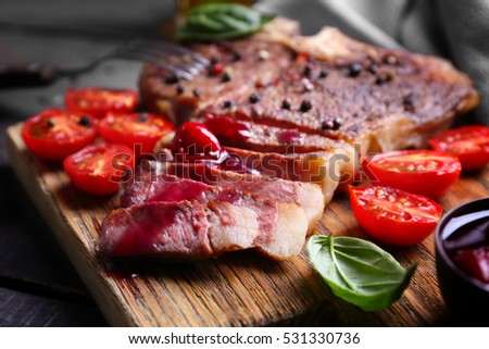 Grilled steak with tomatoes and basil on cutting board, closeup