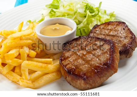 Grilled steaks, chips and vegetables - stock photo