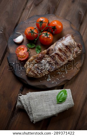 Grilled striploin steak with sea salt and tomatoes, top view, rustic wooden background - stock photo