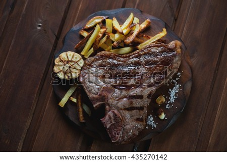 Grilled T-bone beefsteak served with roasted potato, top view