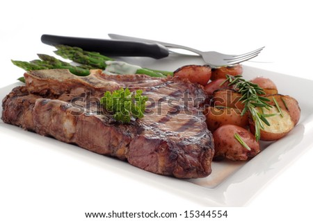 Grilled t-bone steak with rosemary potatoes and asparagus. - stock photo