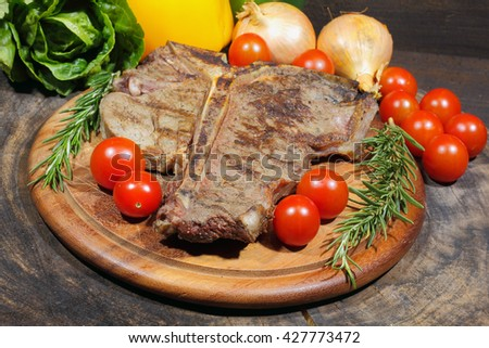 Grilled T bone steak with rosemary tomatoes, onions and pepper garnished, on a rustic wooden chopping board - stock photo