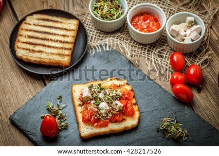 Grilled toasted bread with roasted tomatoes, feta cheese and radish sprouts. - stock photo