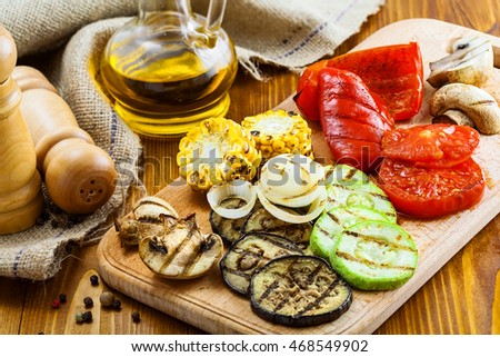 Grilled tomato, corn, eggplant, mushroom, bell pepper, marrow and onion on a table. Healthy prepared food for delicious dinner.