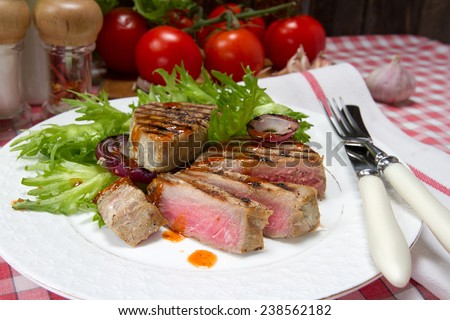 Grilled tuna and onion rings with spicy sauce - stock photo