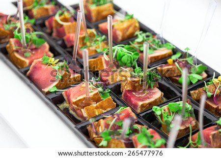 Grilled tuna chunks served with fresh green herbs on black starter plate.  - stock photo