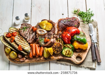 Grilled vegetables and steak with herbs on white table - stock photo