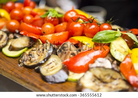 grilled vegetables: cherry tomatoes, peppers, zucchini and eggplant on a wooden board and saucers sauce in the background