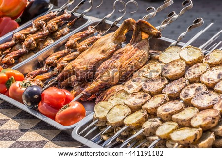 Grilled vegetables on a skewer during the cooking process on the grill with grates and aromatic smoke. In the style of Oriental cuisine. - stock photo