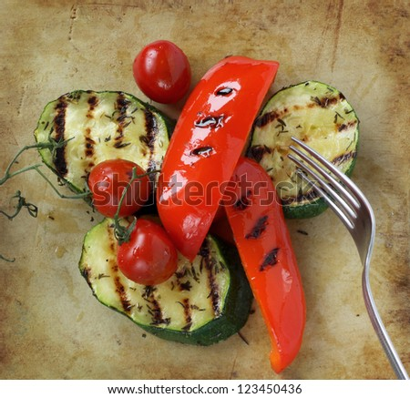 Grilled vegetables on an old rustic stone chopping board - stock photo