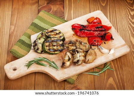 Grilled vegetables on cutting board over wooden table background. View from above - stock photo