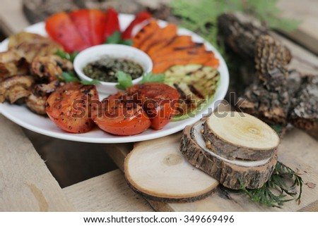 Grilled vegetables on the white plate. grilled vegetbles on the wooden background. Grilled onion.  Grilled pepper. grilled mushrooms. Grilled vegetable marrow.grilled vegetables in a wood.