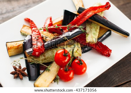 Grilled vegetables on white plate. Close-up of white plate with grilled vegetable strips. Grilled paprika, eggplant and vegetable marrow with cherry tomato on white plate top view. - stock photo