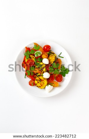 Grilled vegetables with mozzarella cheese. Cherry tomatoes, pepper, eggplant, zucchini served with parsley in white plate on white background with fresh herbs. Top view. - stock photo