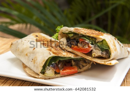 Grilled vegetarian wrap on a white plate outdoors in the tropics