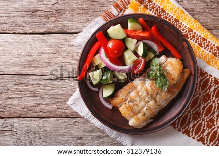 Grilled white fish and fresh vegetable salad on a plate. horizontal view from above  - stock photo