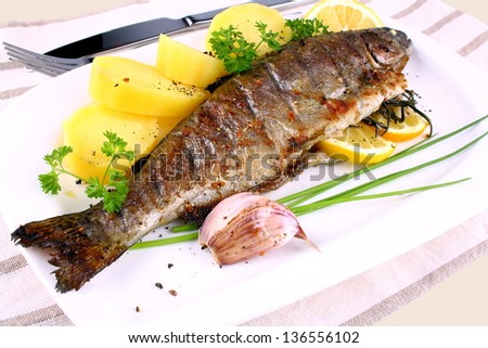 Grilled whole trout, potato, lemon and garlic, close up - stock photo