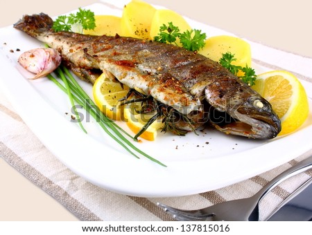 Grilled whole trout with potato, lemon and garlic, close up