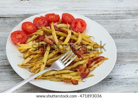 Grilled yellow beans with grilled bacon on the white plate decorated with tomatoes