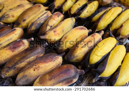 Grilling banana in stainless steel stick ready for dessert - stock photo