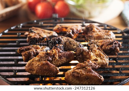 Grilling chicken wings on barbecue grill. Selective focus - stock photo