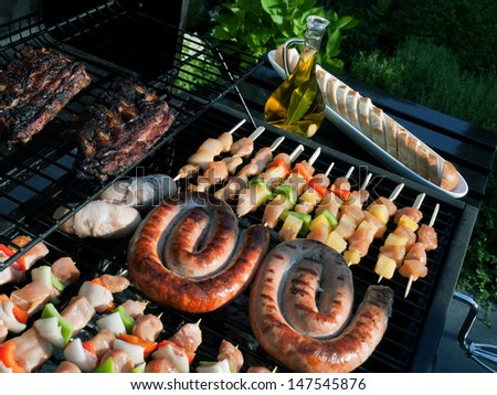 Grilling food on the BBQ on a summer day in the garden - stock photo