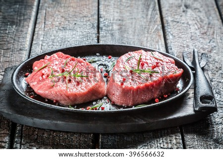 Grilling fresh piece of red meat with rosemary - stock photo