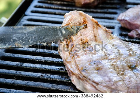 Grilling Lamb on the Grill and Using Grilling Tongs - stock photo