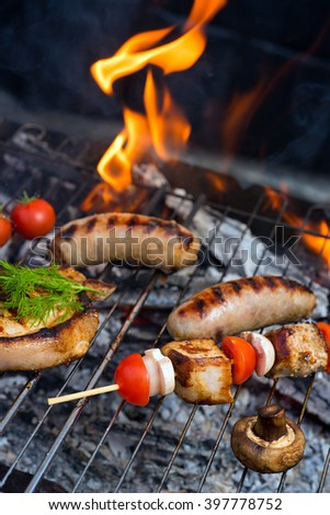 Grilling sausages on barbecue grill with fire - stock photo