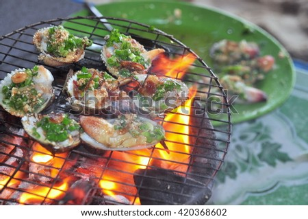 Grilling shellfish and seafood on hot fire - stock photo