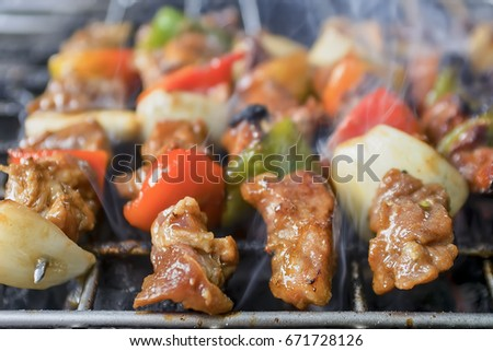Grilling skewered meat, onion, green pepper, and tomatoes