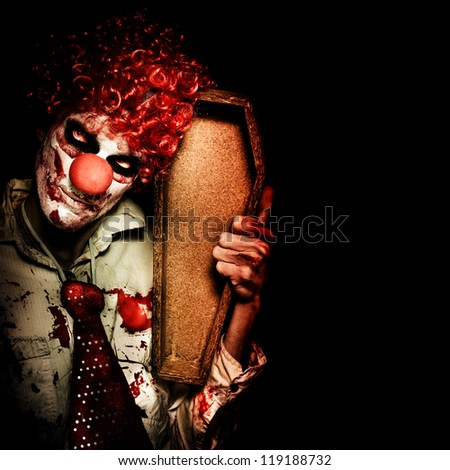 Grim Reaper Death Clown Holding Empty Wooden Casket When Collecting The Dead On Dark Background - stock photo